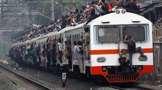 ジャカルタの電車は乗車率250%。屋根に乗ったりはみ出している人はもちろん無賃乗車。